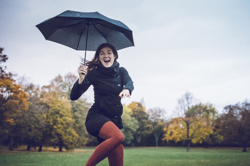 Portrait of happy young woman with umbrella dancing in autumnal park - JSCF00030