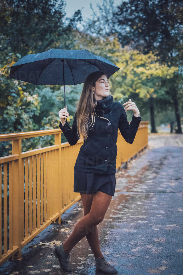 Young woman with umbrella standing on a bridge in autumn - JSCF00033 - Jonathan Schöps/Westend61