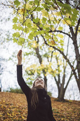 Happy young woman in autumnal forest - JSCF00039