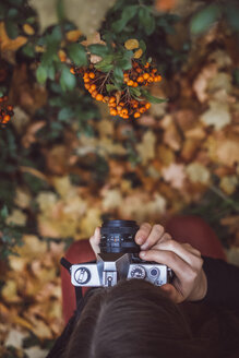 Young woman taking photos in autumnal nature with old camera, top view - JSCF00042
