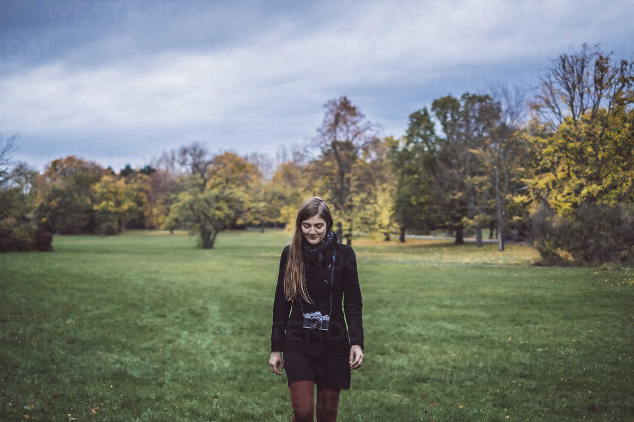 Young woman with camera walking on a meadow in autumnal park - JSCF00048 - Jonathan Schöps/Westend61