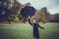 Young woman dancing with umbrella in autumnal park - JSCF00051