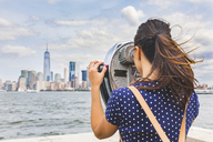 USA, New York, woman looking at Manhattan skyline with coin-operated binoculars - WPEF00046