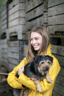 Smiling woman on a farm standing at wooden boxes holding dog - PESF00957