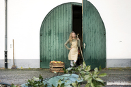Smiling woman on a farm standing at crate with apples - PESF00969
