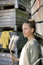 Thoughtful woman leaning against wooden boxes - PESF00972