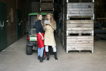Two happy women using tablet in storehouse of a farm - PESF00978