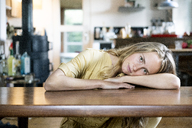 Portrait of blond woman lying on table - PESF00984