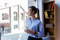 Young woman with coffee cup looking out of office window - VABF01462