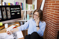 Young woman working in architecture office, talking on the phone - VABF01480