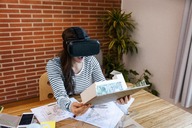 Young woman working in architecture office, looking at model with VR goggles - VABF01516
