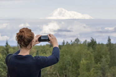 USA, Alaska, young woman photographing with smartphone Mount Denali - MMAF00273
