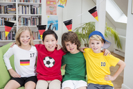 Four children in football shirts sitting on couch with arms around - NEKF00015