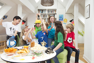 Group of kids watching soccer world championship with table full of sweets and snacks - NEKF00018