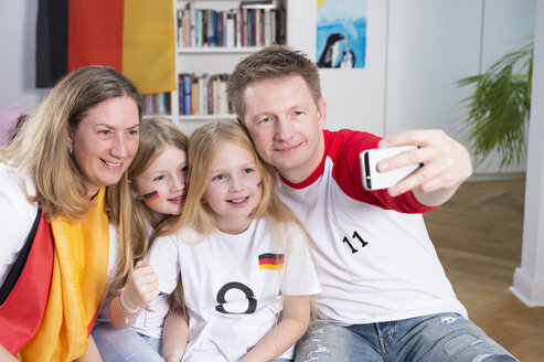 Family watching football world cup, taking a smartphone selfie - NEKF00027