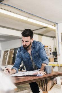 Man looking at draft in workshop - UUF12675