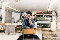Man sitting on chair in workshop - UUF12684