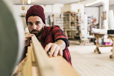 Man examining wood in workshop - UUF12714