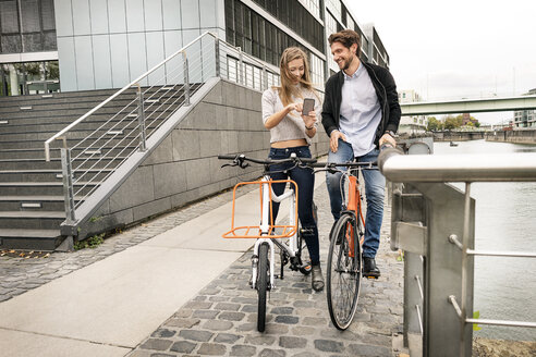 Smiling couple with bicycles and cell phone in the city - PESF00992