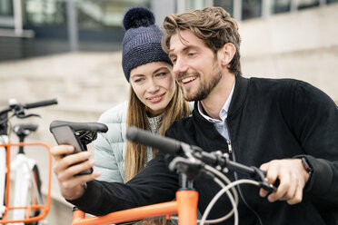 Smiling couple with bicycles and cell phone in the city - PESF00995