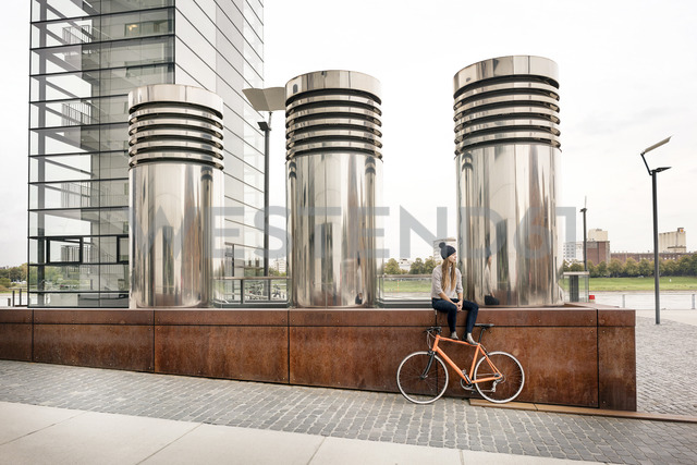 Young woman with bicycle having a break in the city - PESF00998 - Peter Scholl/Westend61