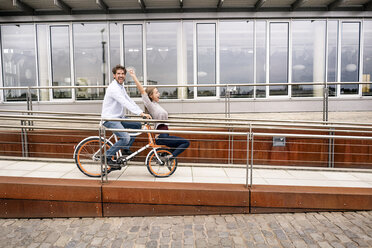 Carefree couple riding bicycle in the city - PESF01001