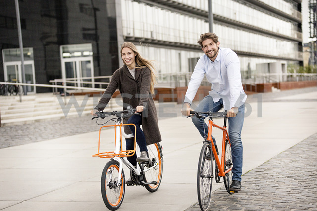 Smiling couple riding bicycle in the city - PESF01004 - Peter Scholl/Westend61