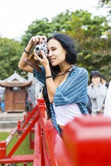 Vietnam, Hanoi, young woman taking a picture with old-fashioned camera - WPEF00050