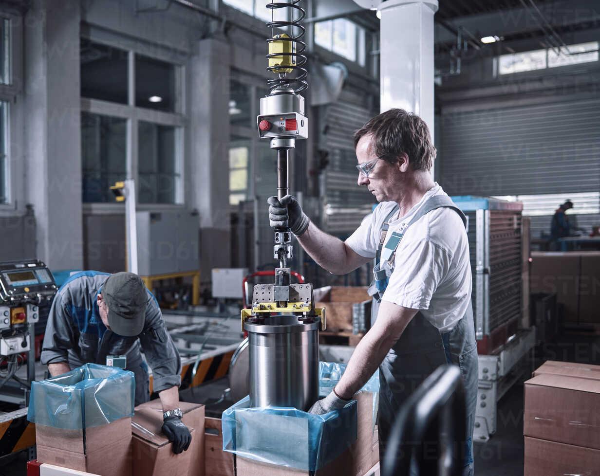 Worker using indoor crane for lifting metalsocket from cardboard box - CVF00131 - Christian Vorhofer/Westend61