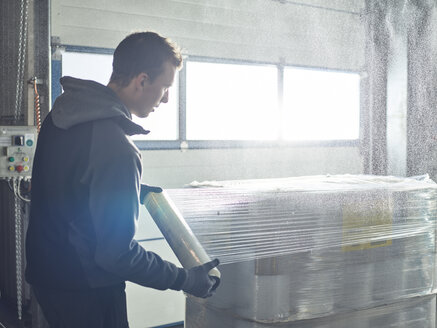 Worker closing freight with foil - CVF00134