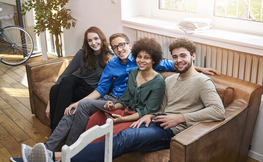 Portrait of smiling young people sitting on sofa with tablet - FMKF04833