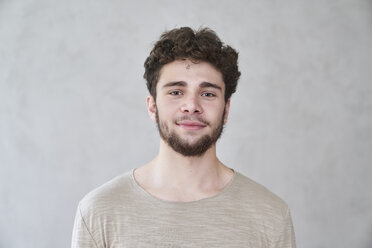 Portrait of smiling young man in front of grey wall - FMKF04839