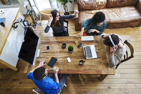 Elevated view of coworkers listening to music at wooden table in office - FMKF04842