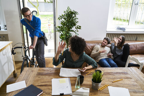 Coworkers waving at young man with bicycle arriving in modern office - FMKF04851