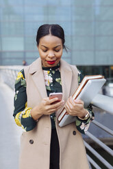 UK, London, fashionable  businesswoman looking at cell phone - MAUF01319