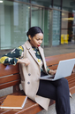 Businesswoman sitting on bench using laptop - MAUF01322