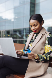 Businesswoman sitting on bench using laptop and credit card - MAUF01325