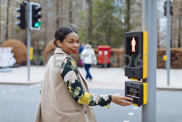 UK, London, portrait of smiling woman pressing button of pedestrian light - MAUF01328