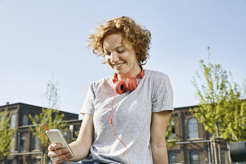 Smiling young woman with headphones using smartphone in urban surrounding - PDF01417
