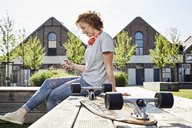 Smiling young woman with headphones and longboard using smartphone in urban surrounding - PDF01420