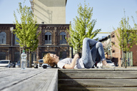 Smiling young woman with longboard lying on bench in urban surrounding - PDF01423