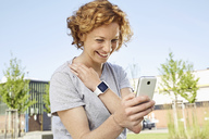 Happy young woman with smartwatch using smartphone in urban surrounding - PDF01426
