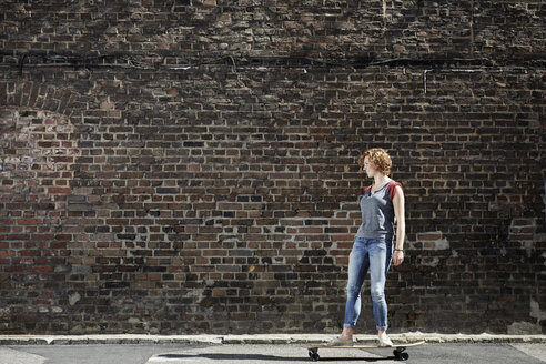 Young woman riding along brick wall with longboard - PDF01429