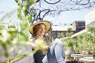 Smiling young woman wearing straw hat relaxing in urban garden - PDF01438
