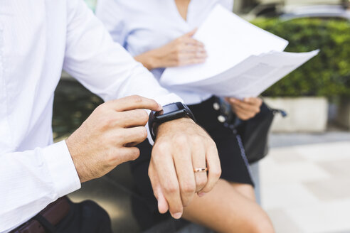 Businessman with smartwatch and businesswoman with documents in the city - WPEF00070