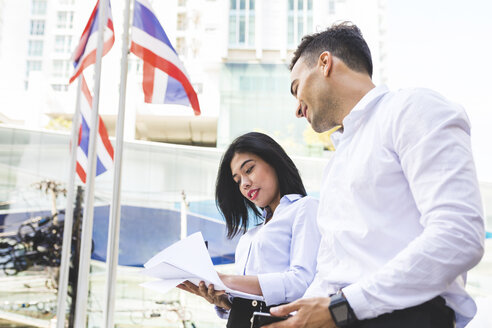 Thailand, Bangkok, businessman and businesswoman in the city looking at documents - WPEF00073