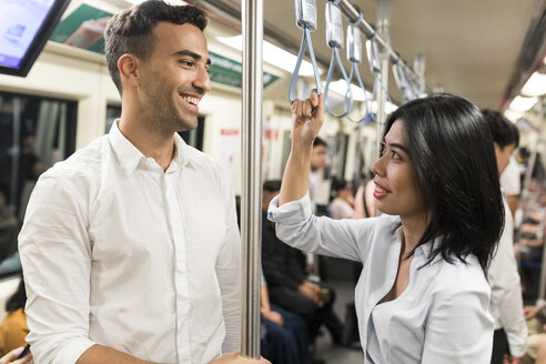 Smiling businessman and businesswoman in the subway - WPEF00082