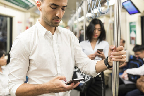 Businessman and businesswoman using cell phones in the subway - WPEF00085