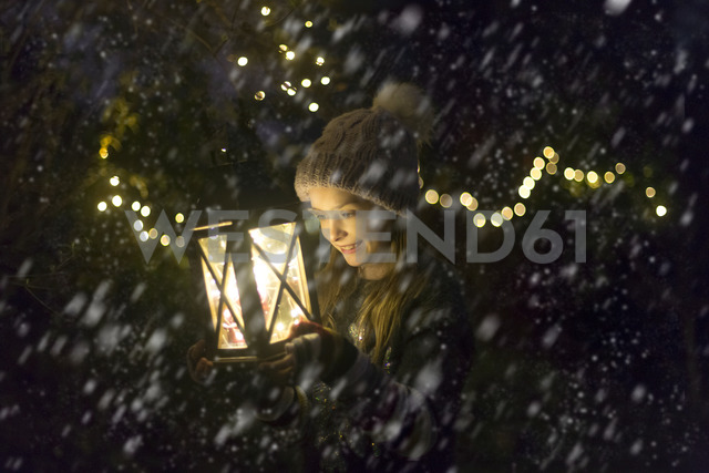 Happy girl with lighted lantern by night at snowfall - SARF03544