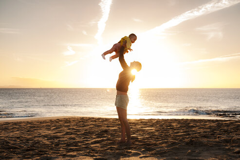 Mother lifting up little daughter on the beach at sunset - DIGF03238